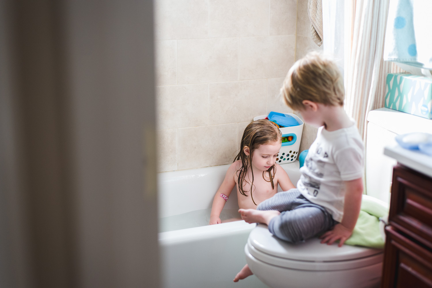 Little brother sits and talks to sister while she takes a bath.