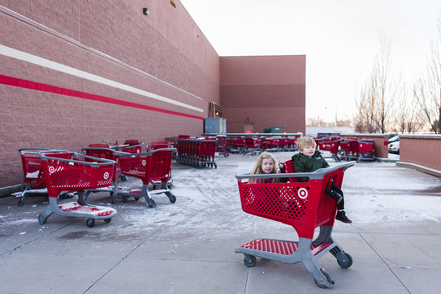 Two kids sit in a cart outside a snowy Target