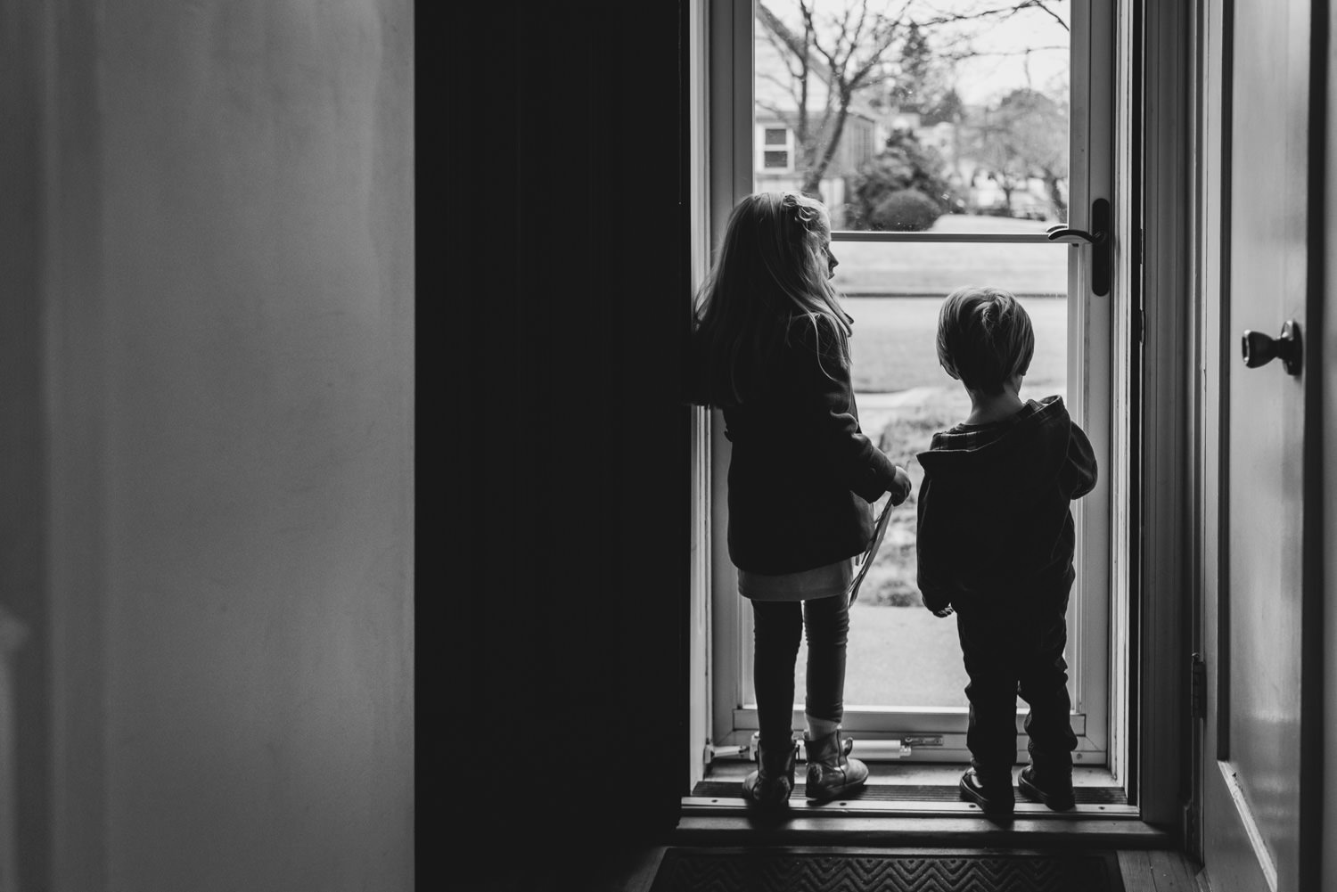 Two children looking out through storm door in Garden City South, NY.