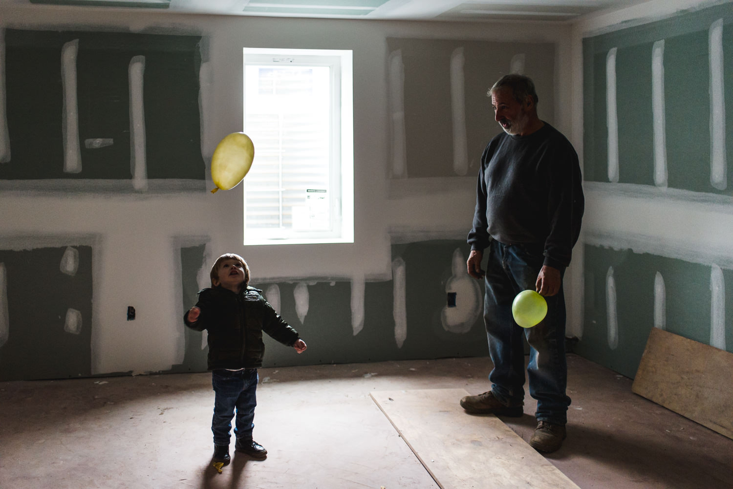 Little boy plays with a yellow balloon in a house under construction in West Hempstead, NY.