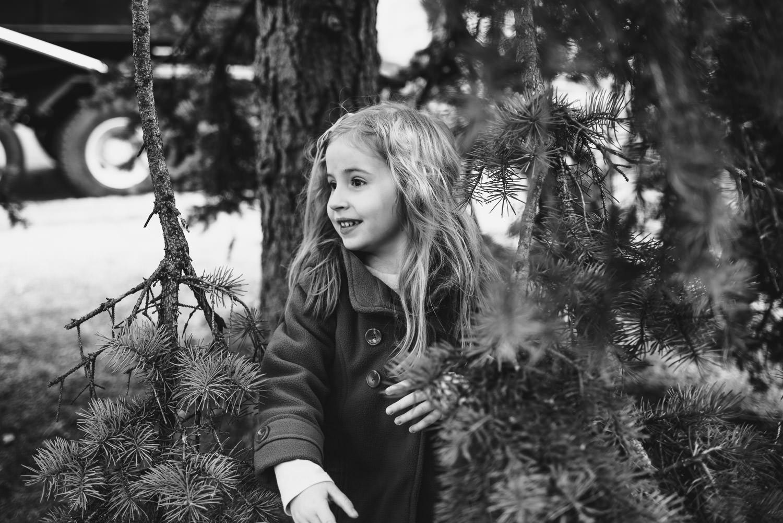 Little girl hiding under a tree in West Hempstead, NY.