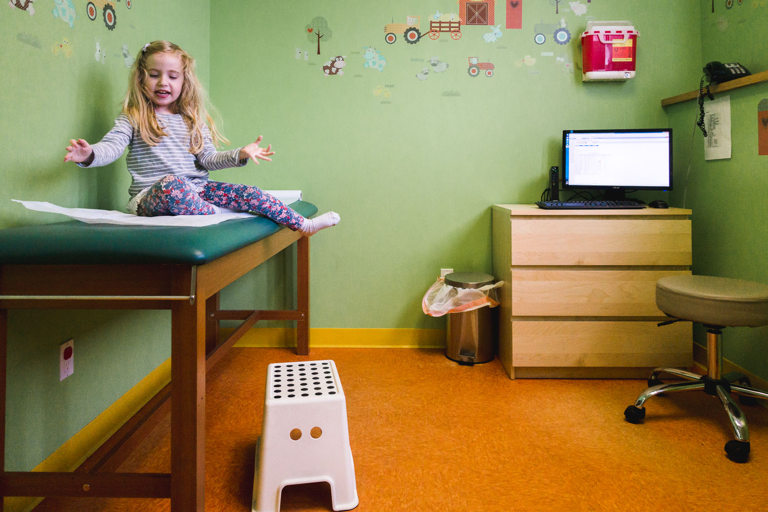 Little girl sits on an examining table in a doctor's office.