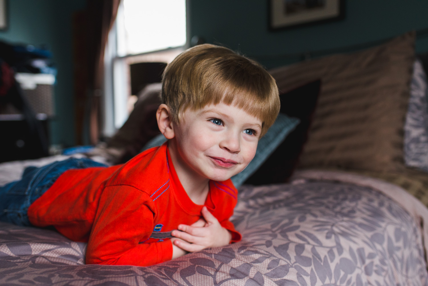 A little boy lying on his parents' bed.