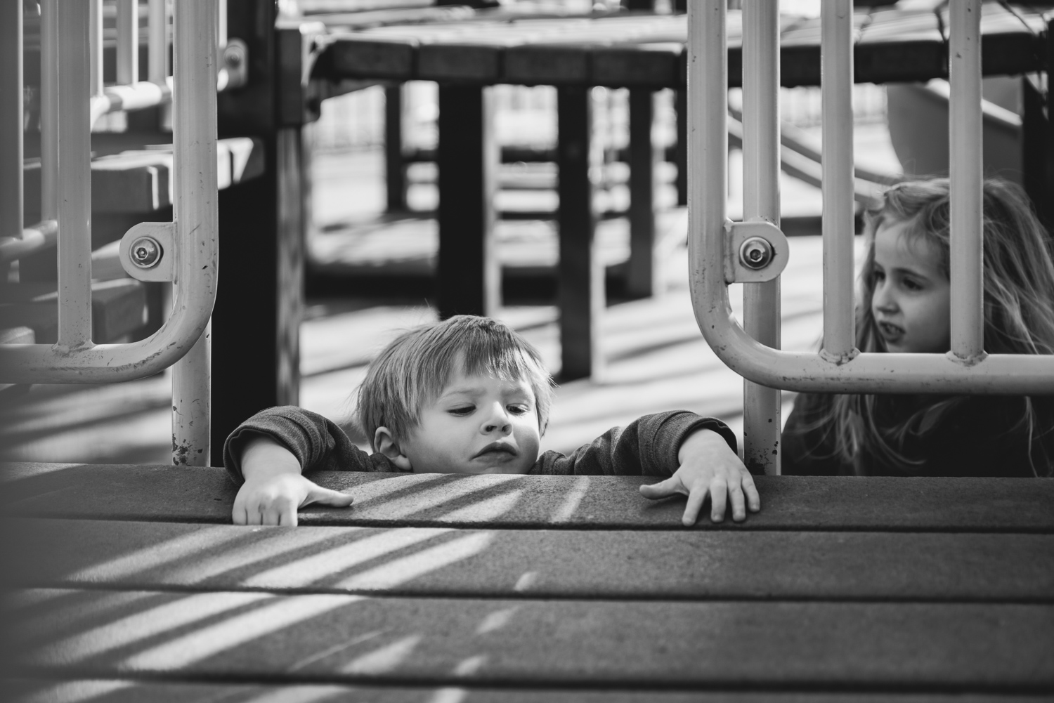 Little brother tries to climb a ladder at the playground.