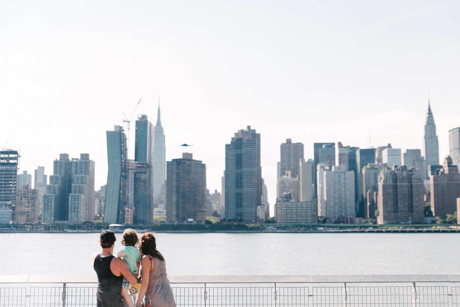A family looks out over the east river at the NYC skyline.
