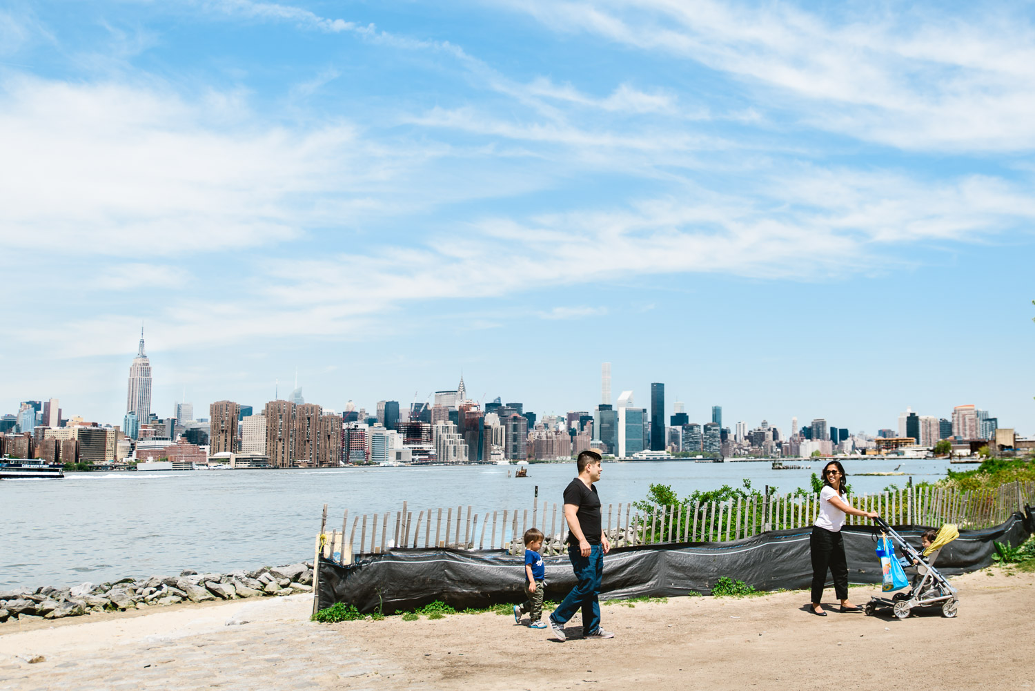 A family walks by the east river in NYC.