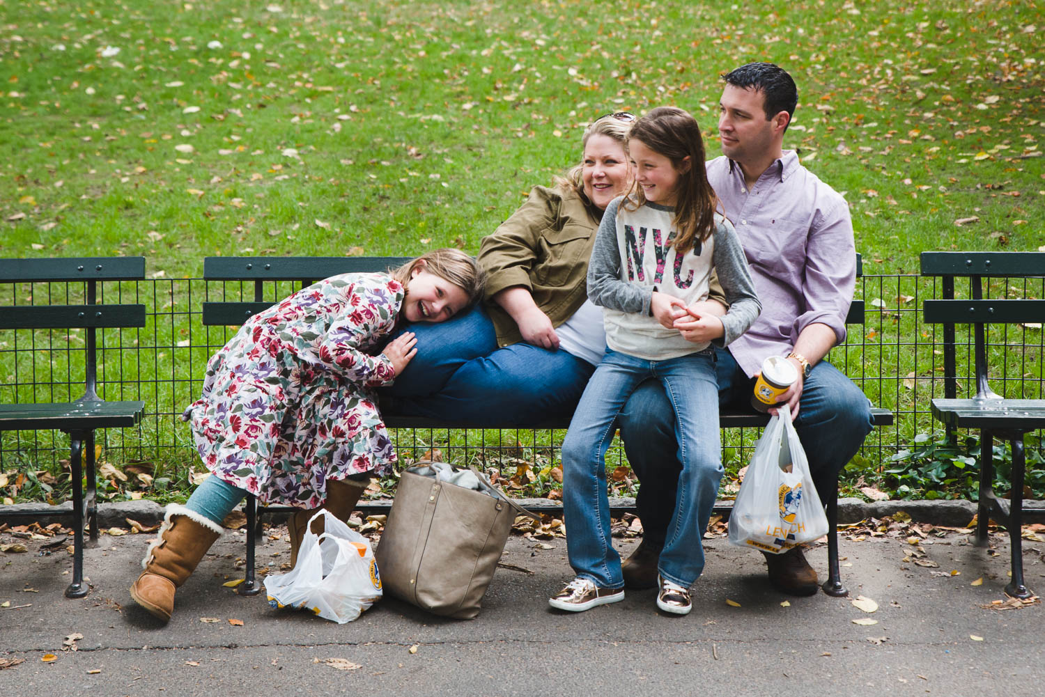 A family relaxes on a park bench in Central Park.