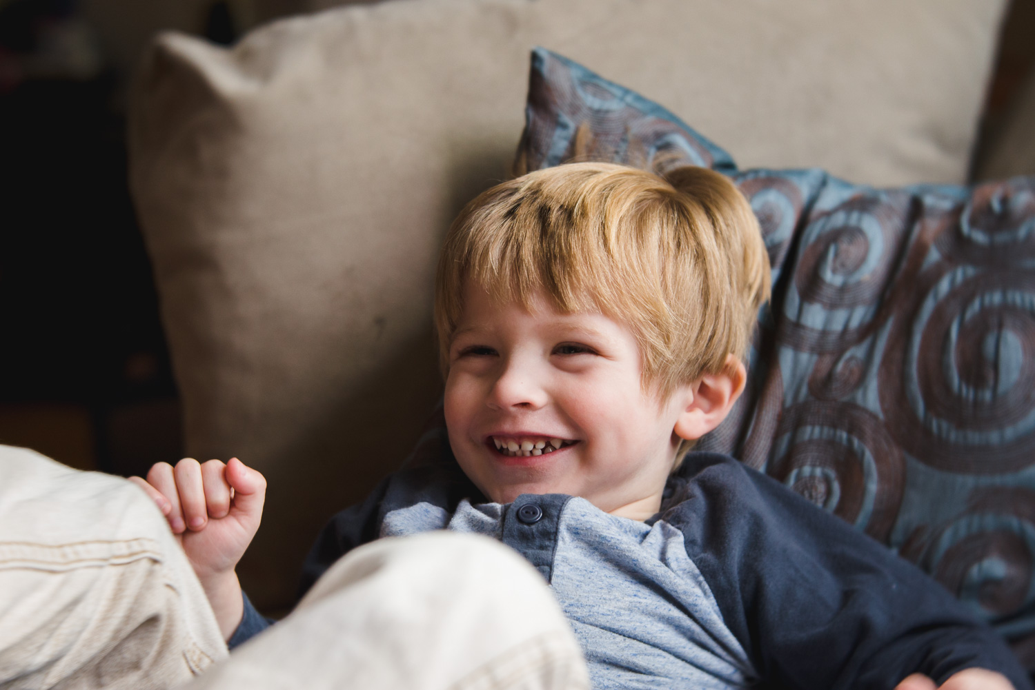 Portrait of a little boy laughing on the couch.