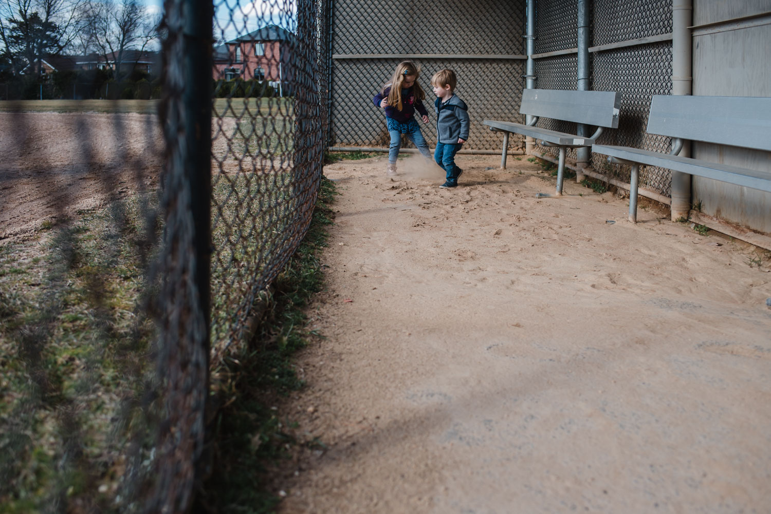 Two children scuffing dirt in a baseball dugout.