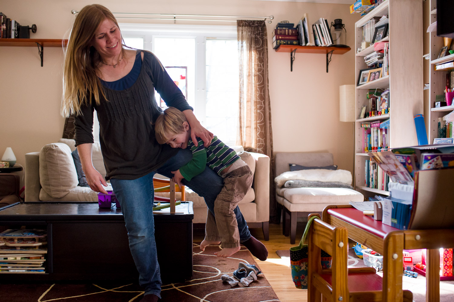 Toddler boy clings to mother's leg in living room.