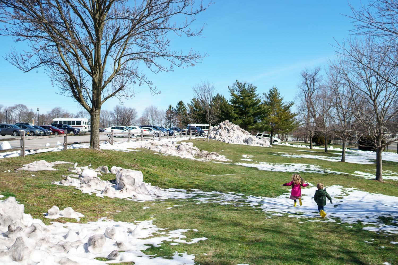 Kids run through a snowy field.
