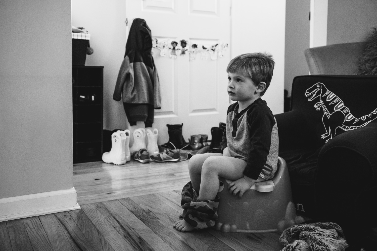 Toddler boy sitting on a potty in the living room.