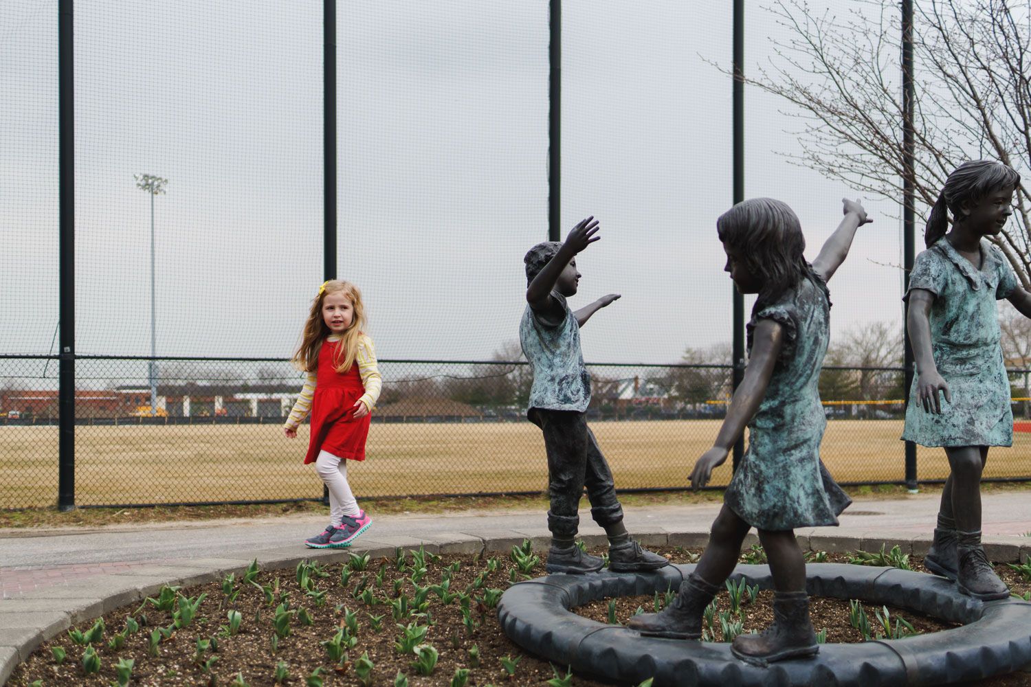 Little girl walks around a statue of three girls at the park.