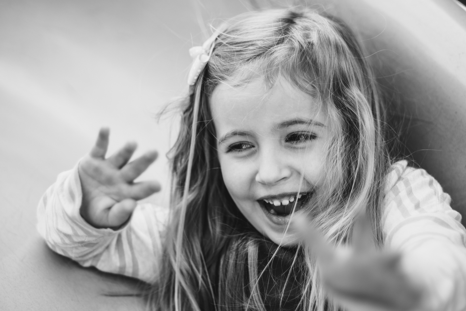 Portrait of a little girl laughing on a slide.