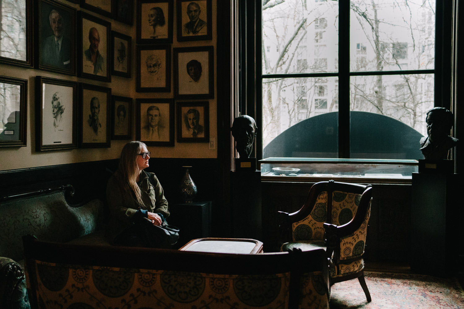 Woman seated at the National Arts Club portrait gallery.