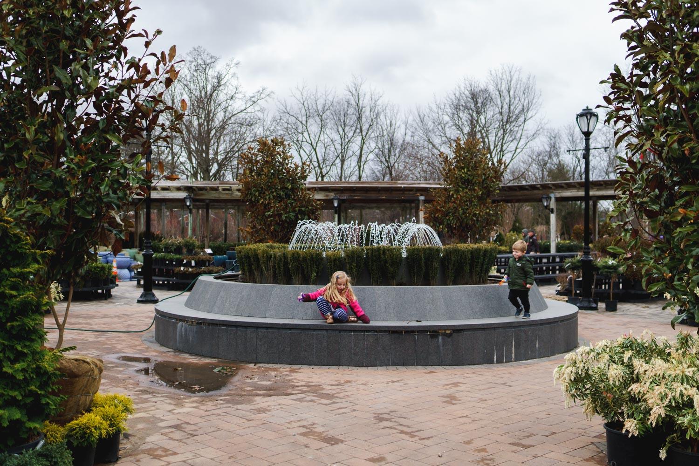 Kids walk around fountain at Hicks Nursery.