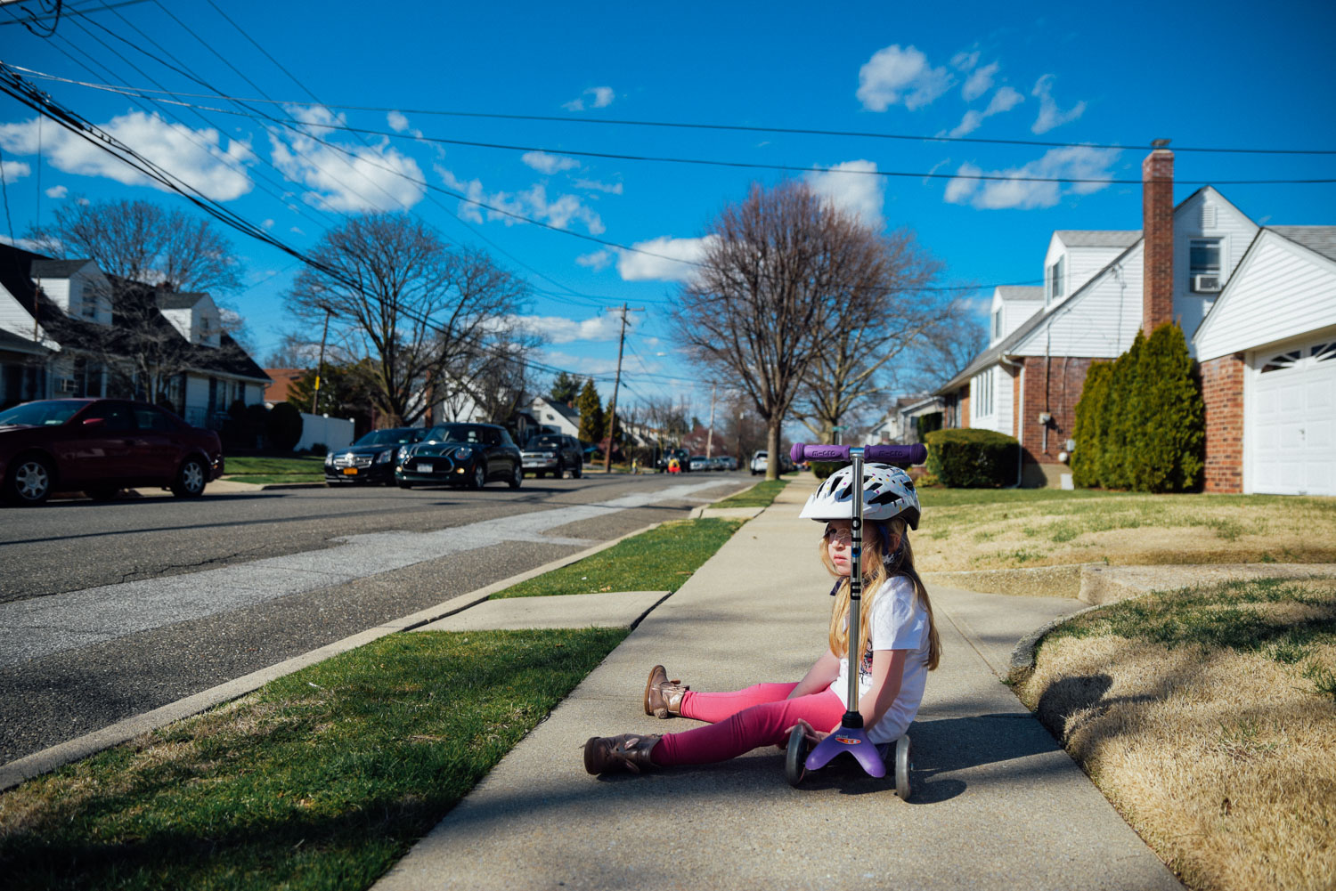 Little girl rests on her scooter in the middle of the sidewalk.