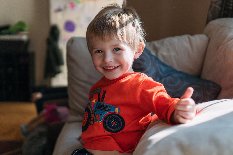 Portrait of a little boy in an orange shirt.