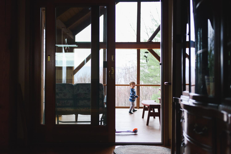 Little boy walking around on porch.