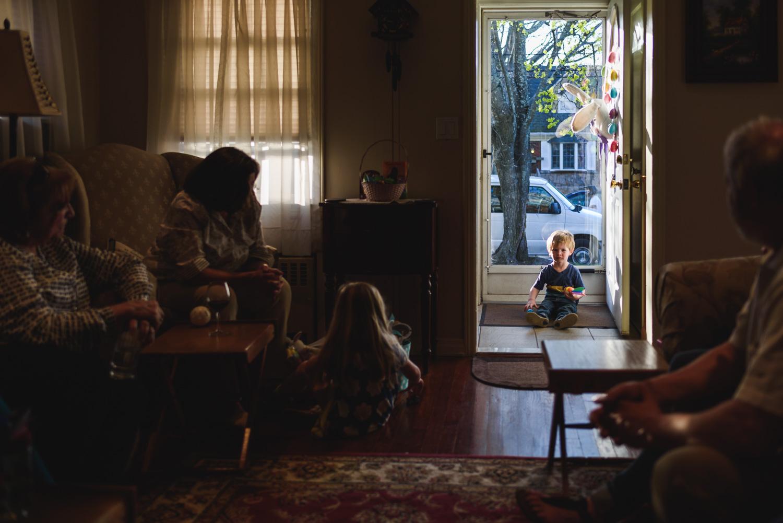 Little boy sits in sunny doorway to living room.