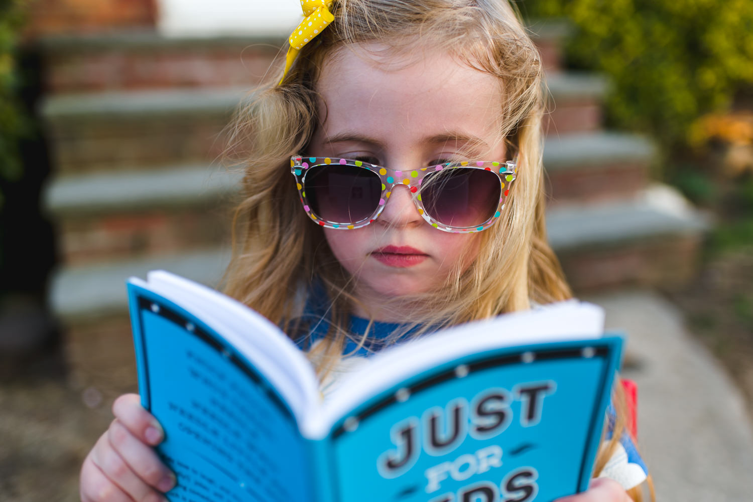 Little girl in sunglasses reading a book outside.
