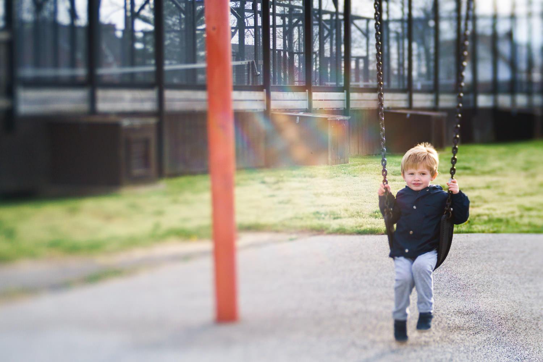 Little boy swings on swing at park.