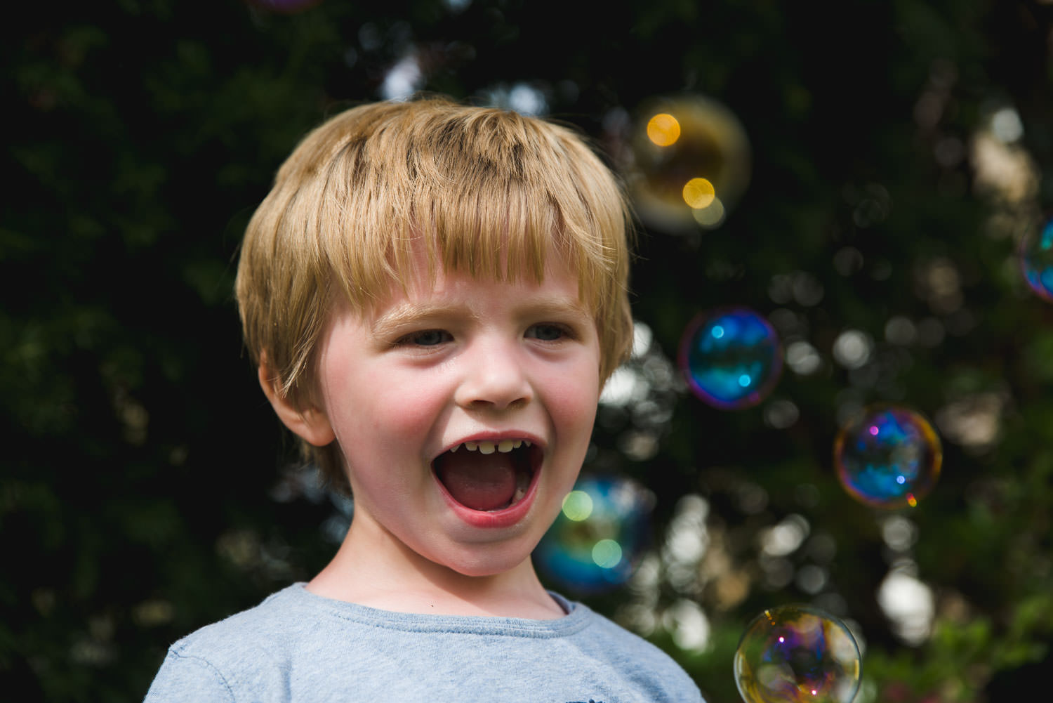 Portrait of a little boy with mouth open surrounded by bubbles.