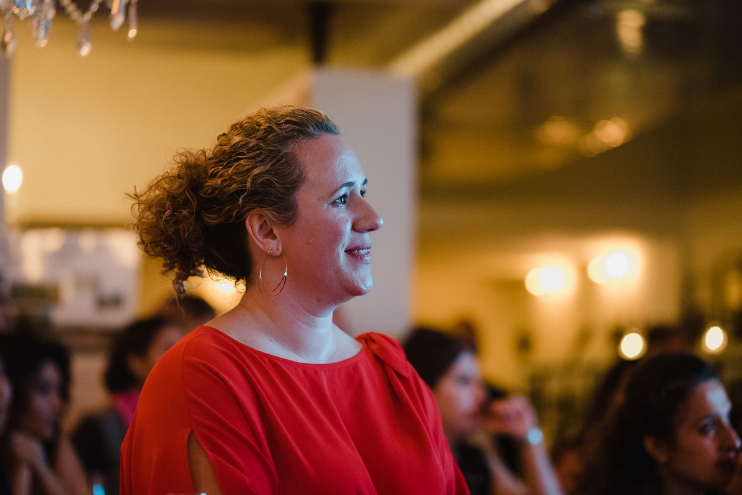 Kate Hintz who organized the City Bash event, looks radiant as she watches her husband make a speech.