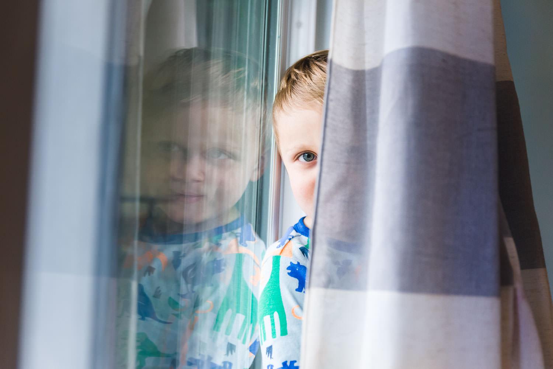 A little boy peeks through the curtains.
