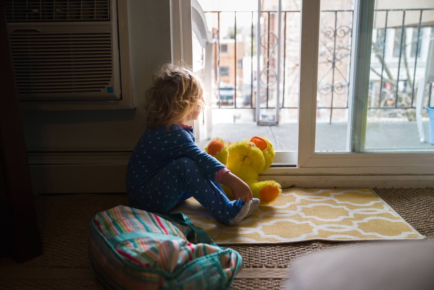 A little girl watches out the sliding glass door of her apartment.