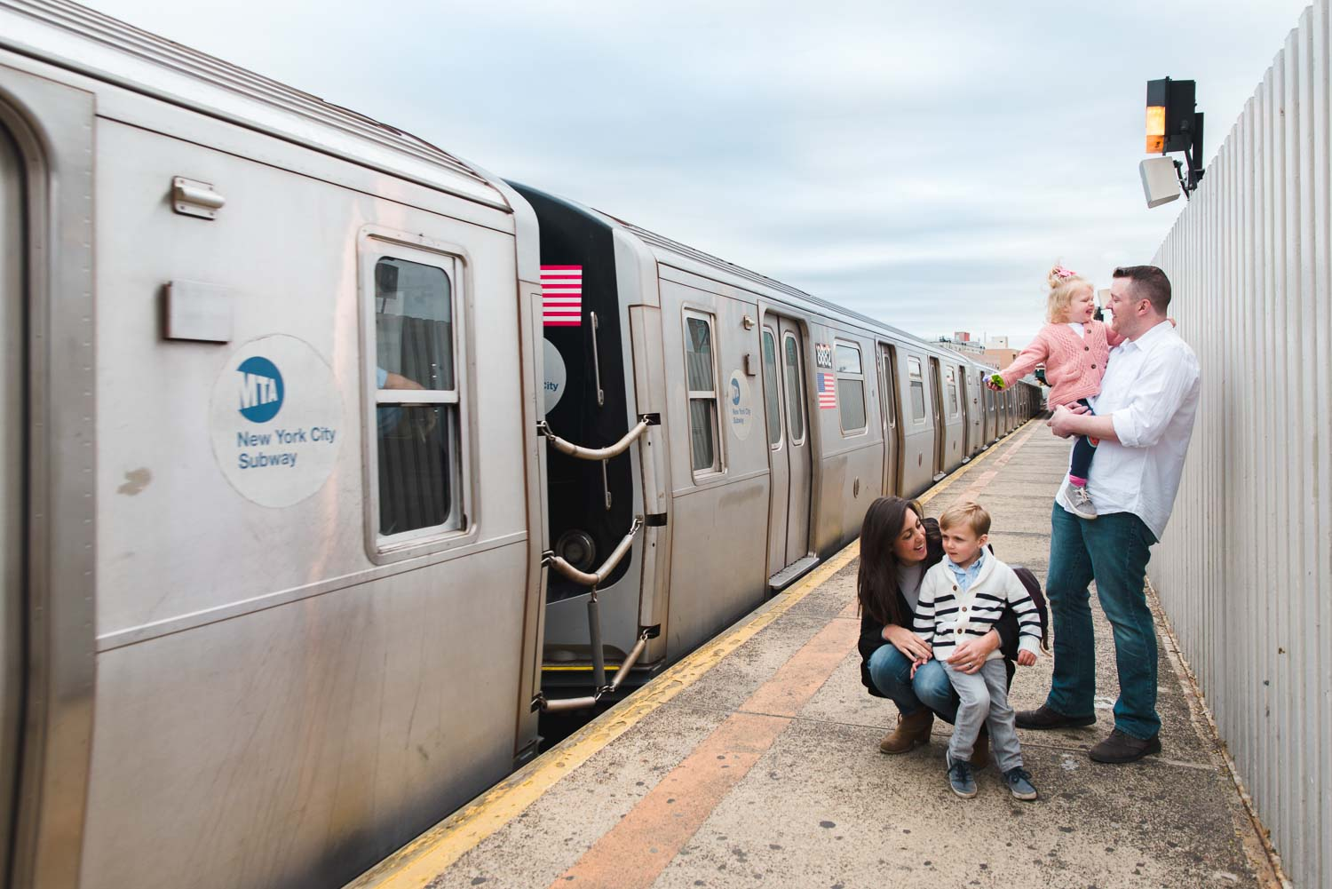 A family waits for the subway in Queens.