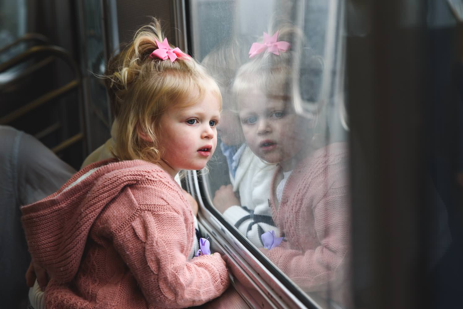 A little girl looks out the window on the subway.