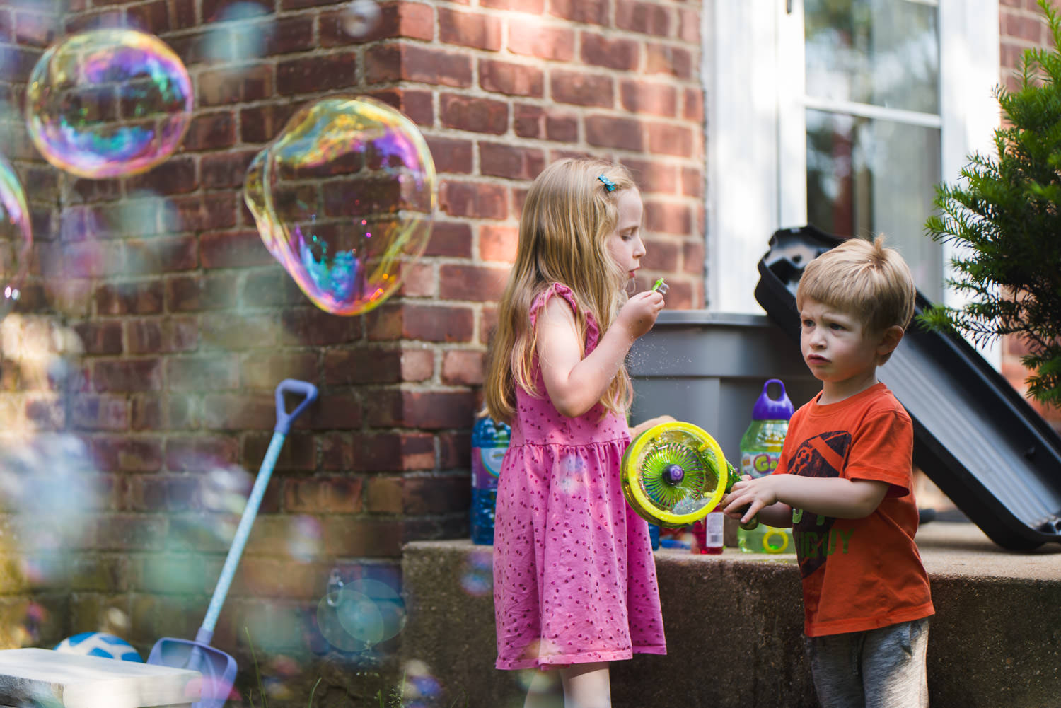 Kids blow bubbles in their front yard.