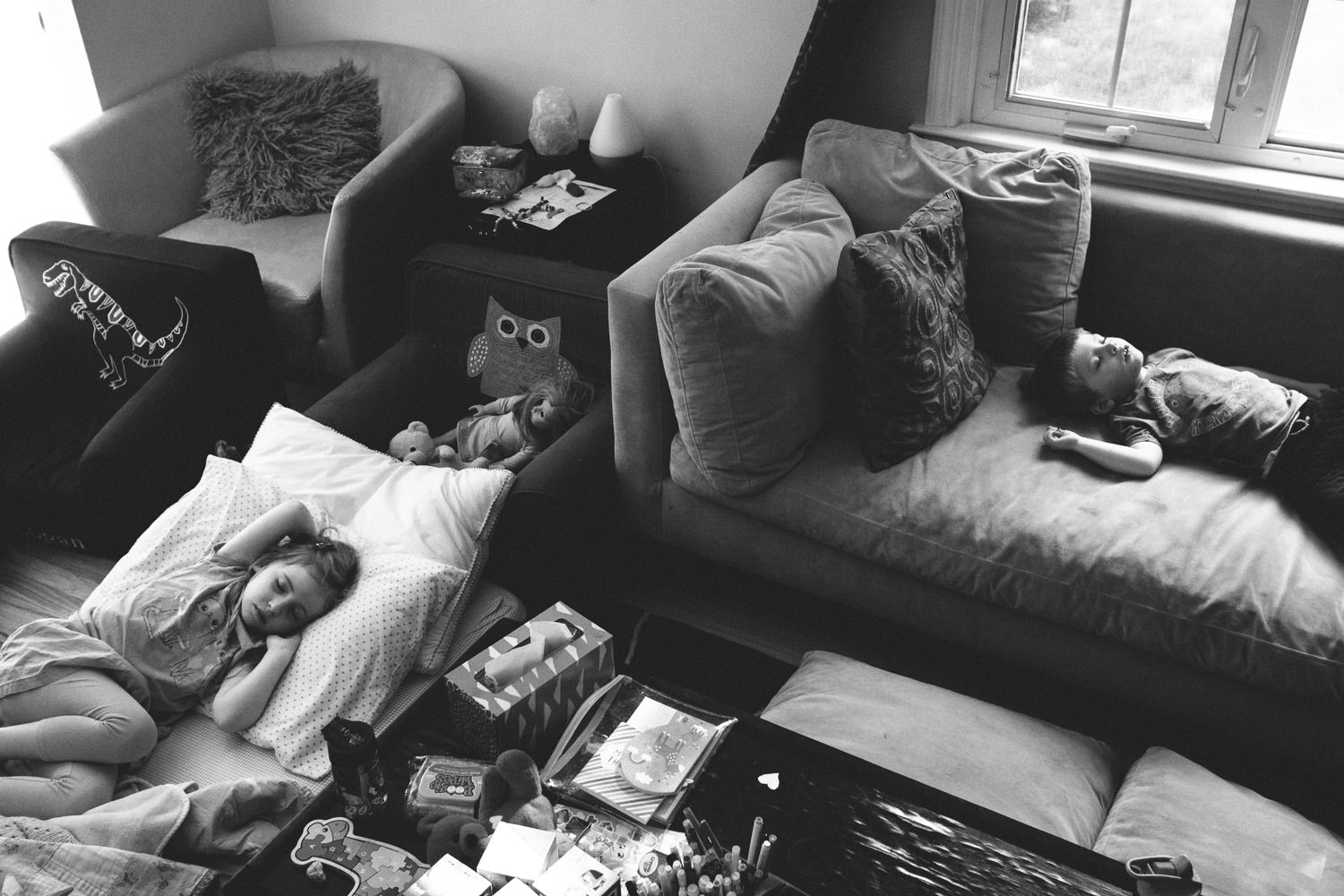 Two children sleep in the living room.