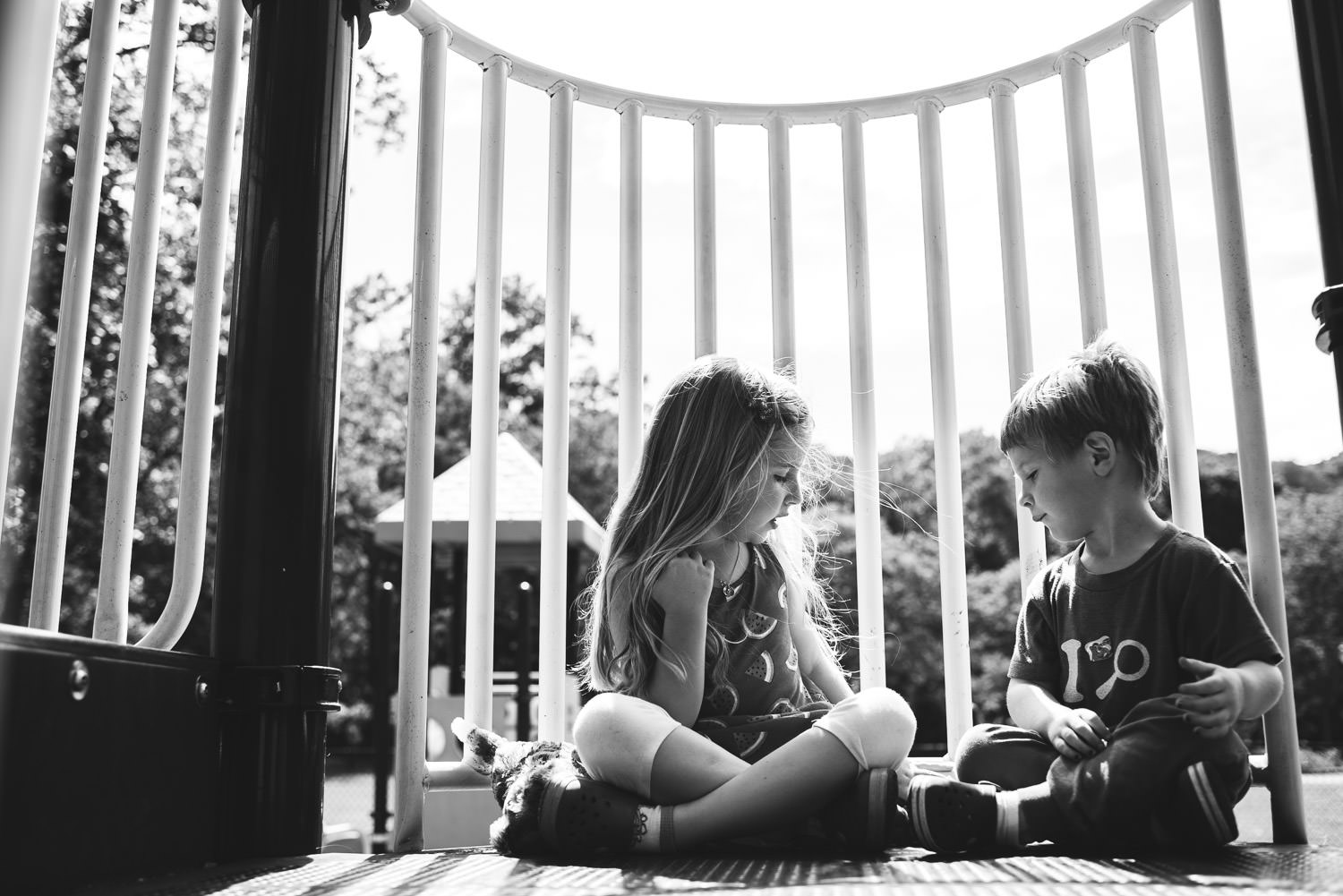 A brother and sister sit peacefully chatting on playground equipment.