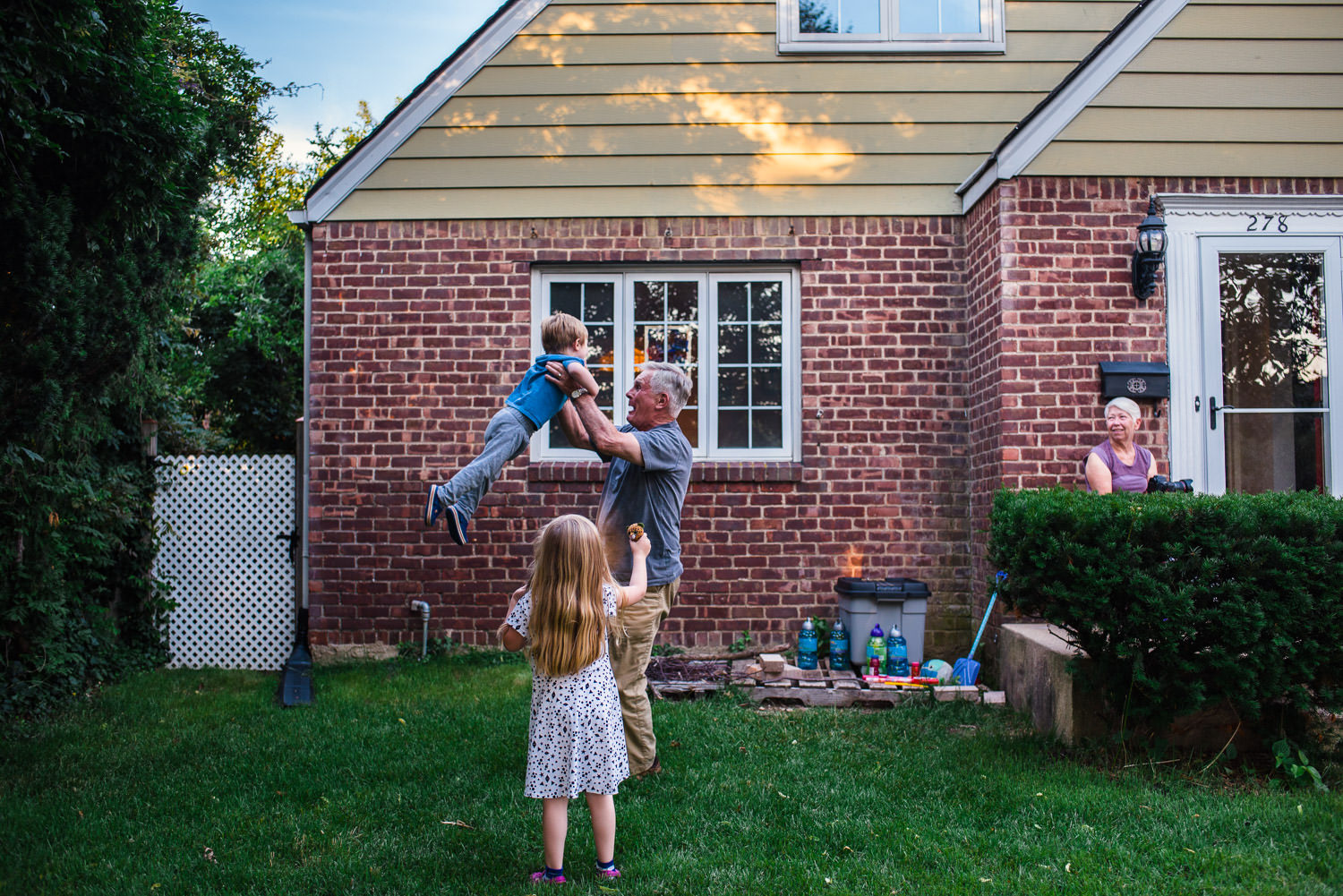 Children spend time with their grandparents in the front yard.