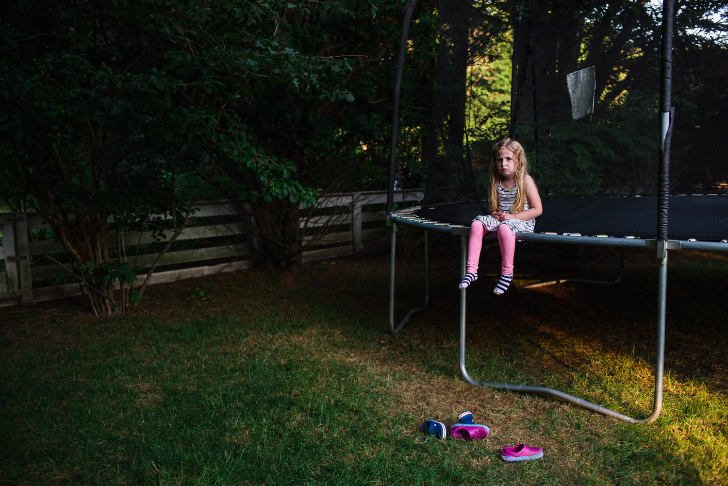 A little girl sits grumpily on the edge of a trampoline.