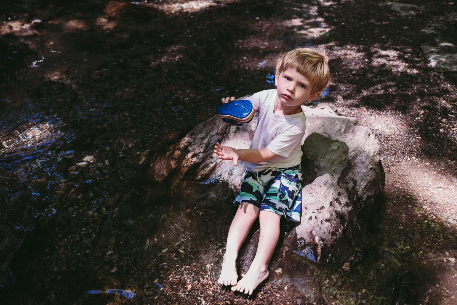 A little boy empties water out of his shoe while sitting on a rock by a creek.