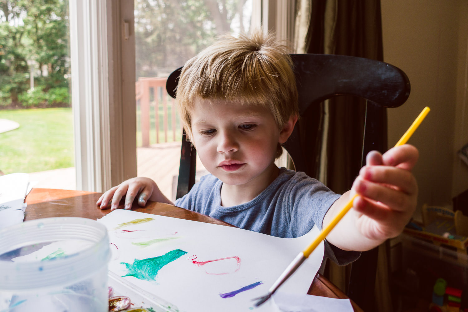 A little boy sits at a table and paints with watercolors.