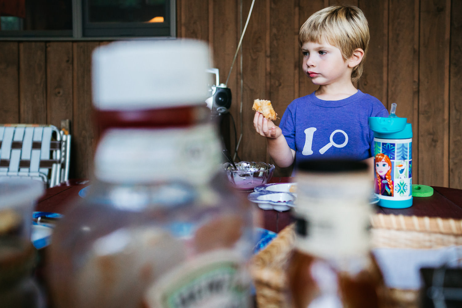 A little boy eats lunch on the porch.