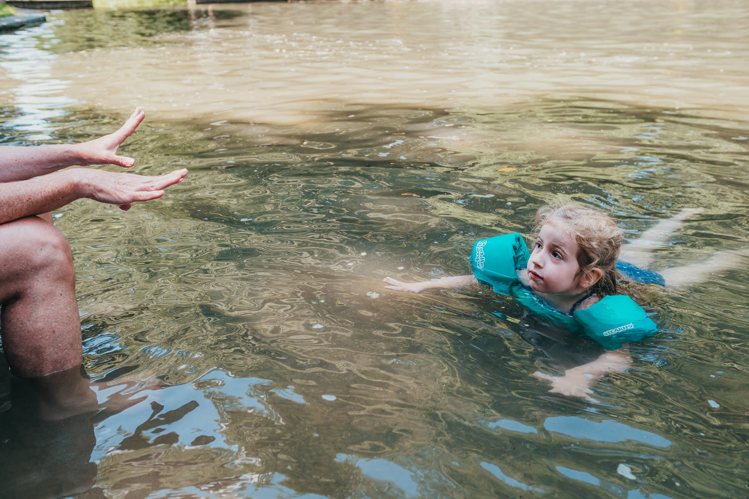 A little girl swims in a swimming hole in Copake.