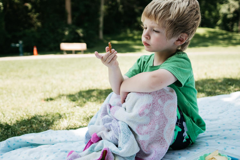 A little boy eats a pretzel on a blanket.