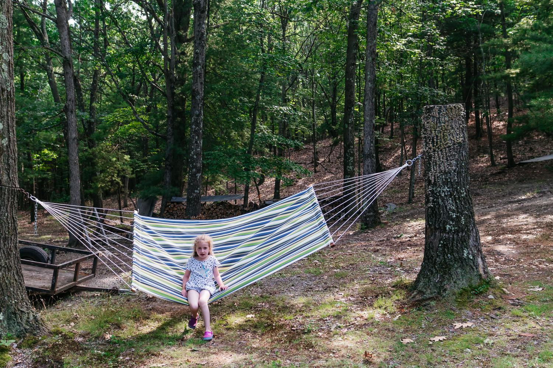 A little girl sits on a hammock in Copake.
