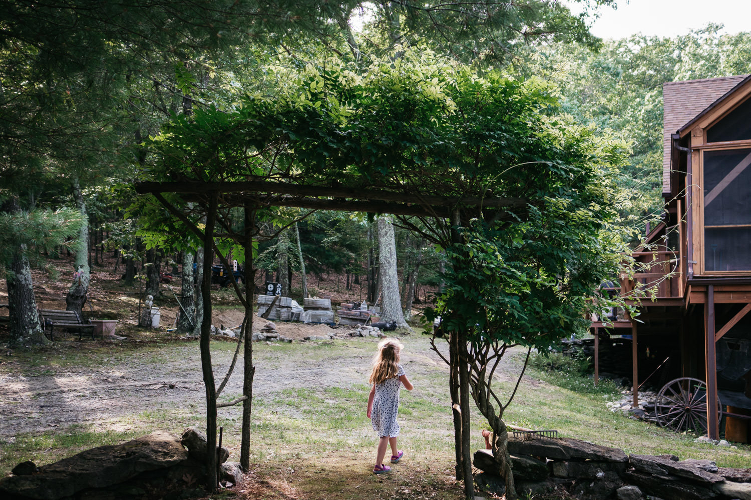 A little girl walks through an archway covered in leaves.