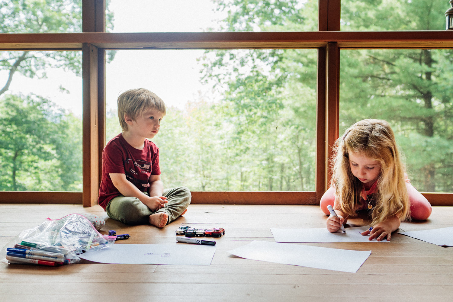 Two kids draw pictures on the floor of a screened in porch.
