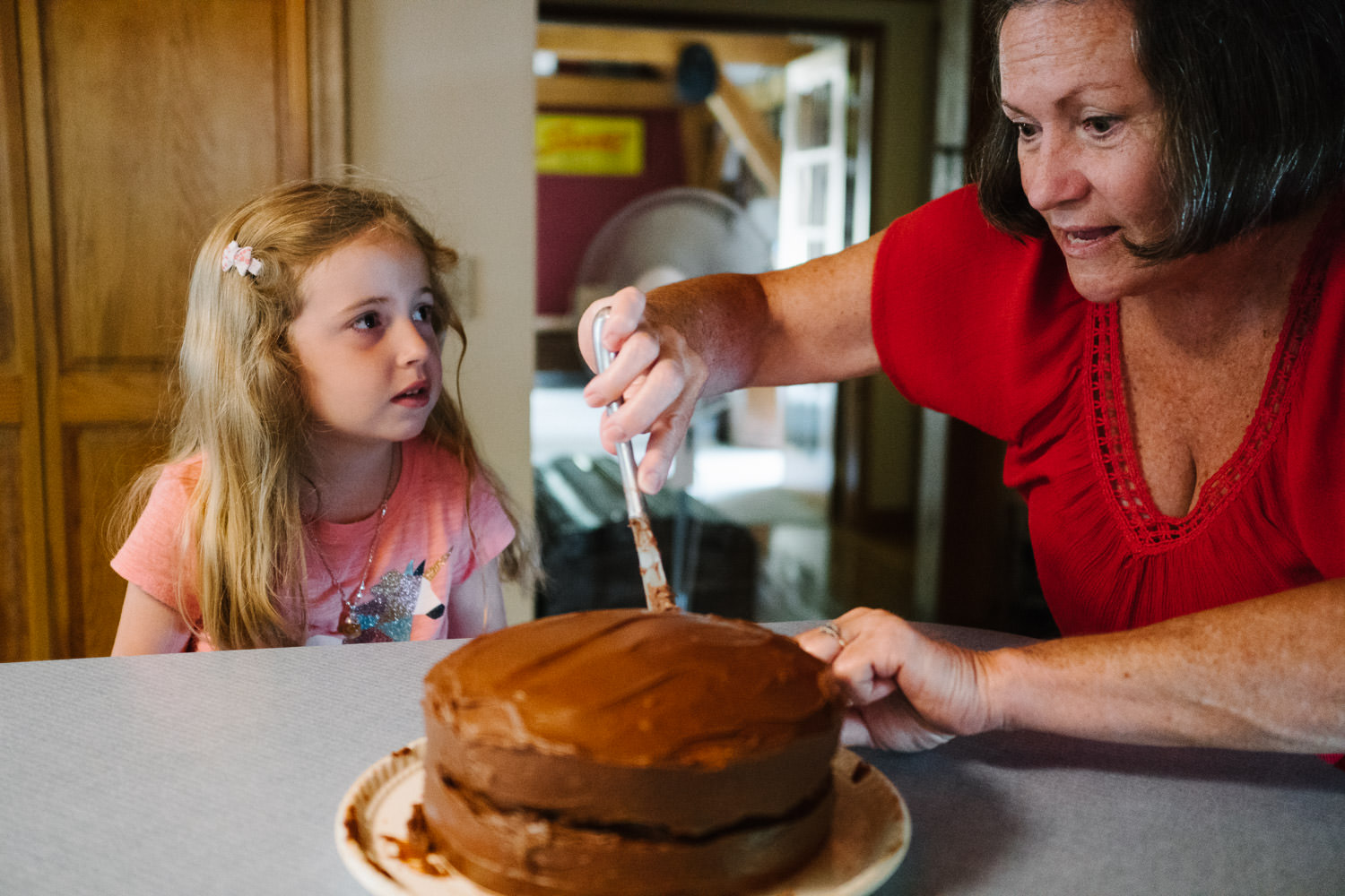 A woman and her granddaughter frost a cake in the kitchen.