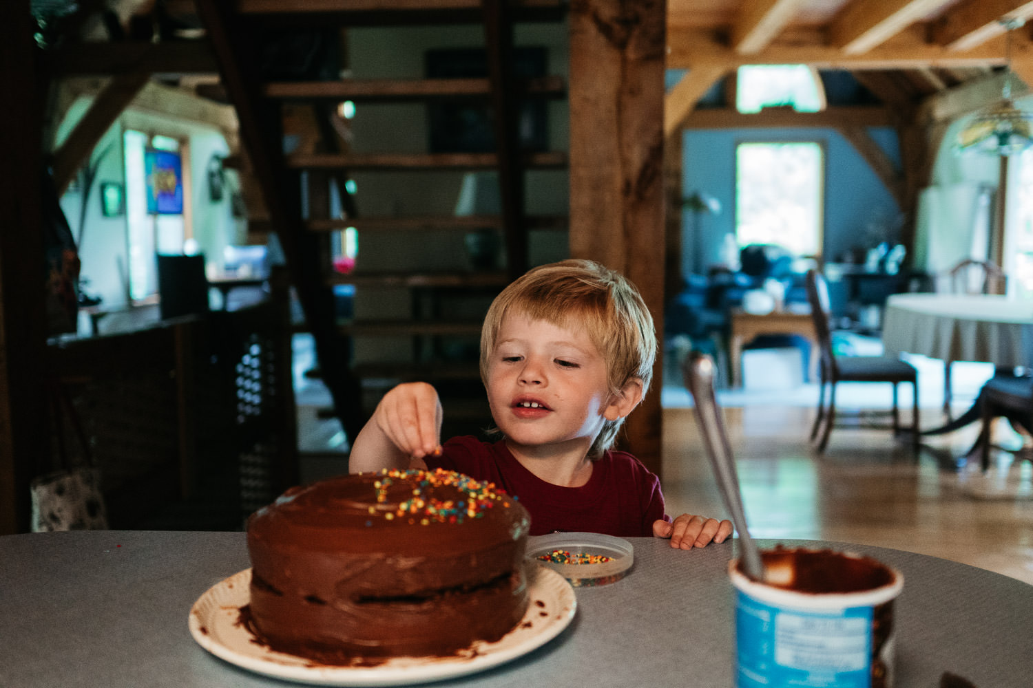 A little boy decorates a cake with sprinkles.