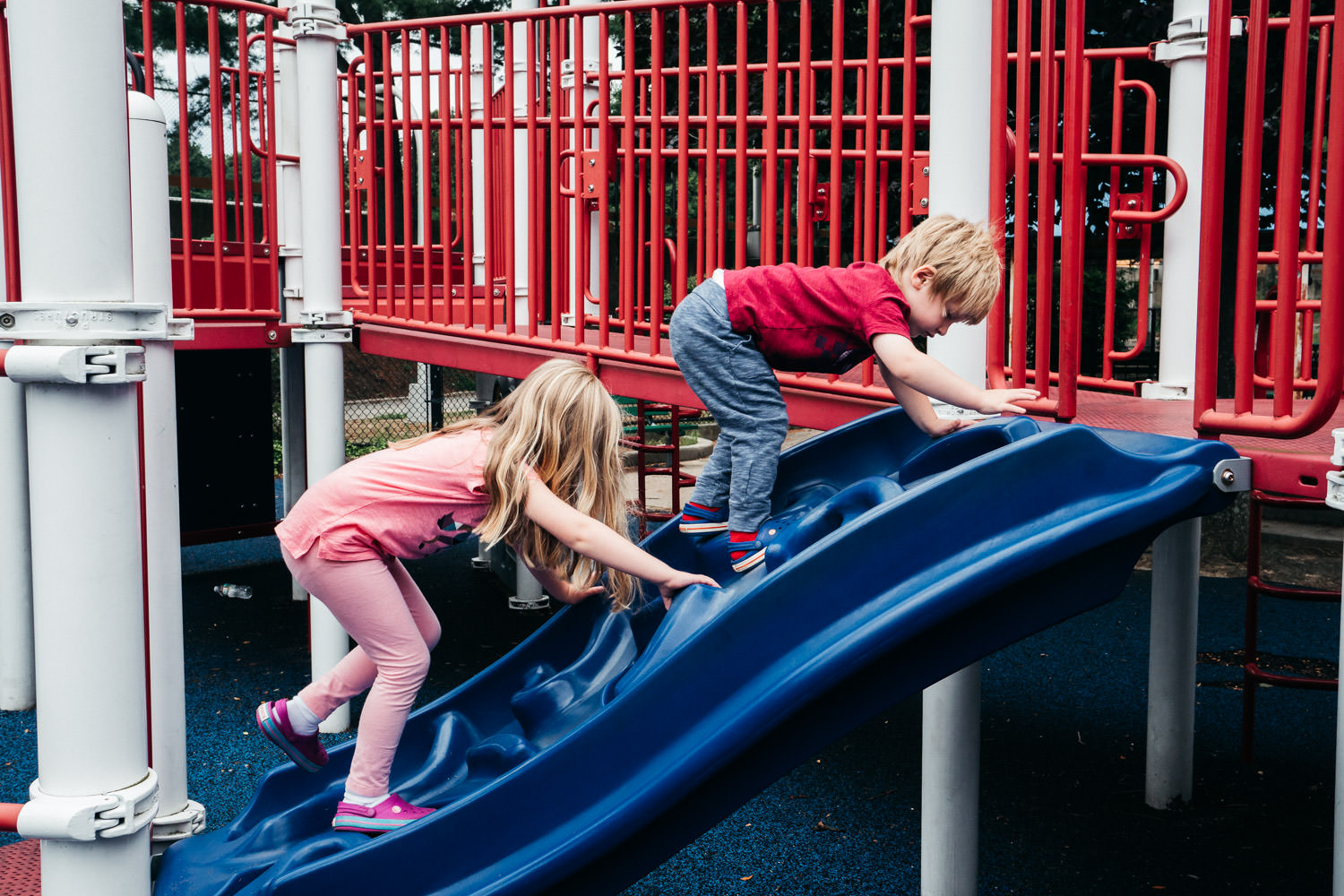 Two kids climb a ladder at a playground in Christopher Morley Park.