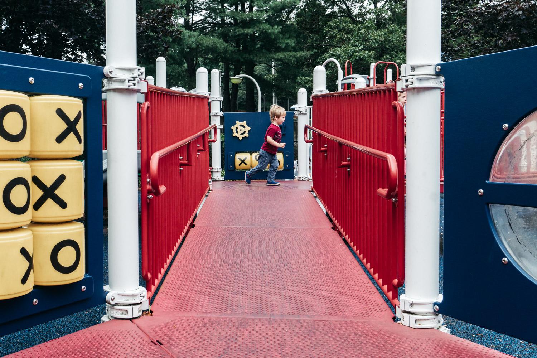 A boy runs across playground equipment at Christopher Morley Park.