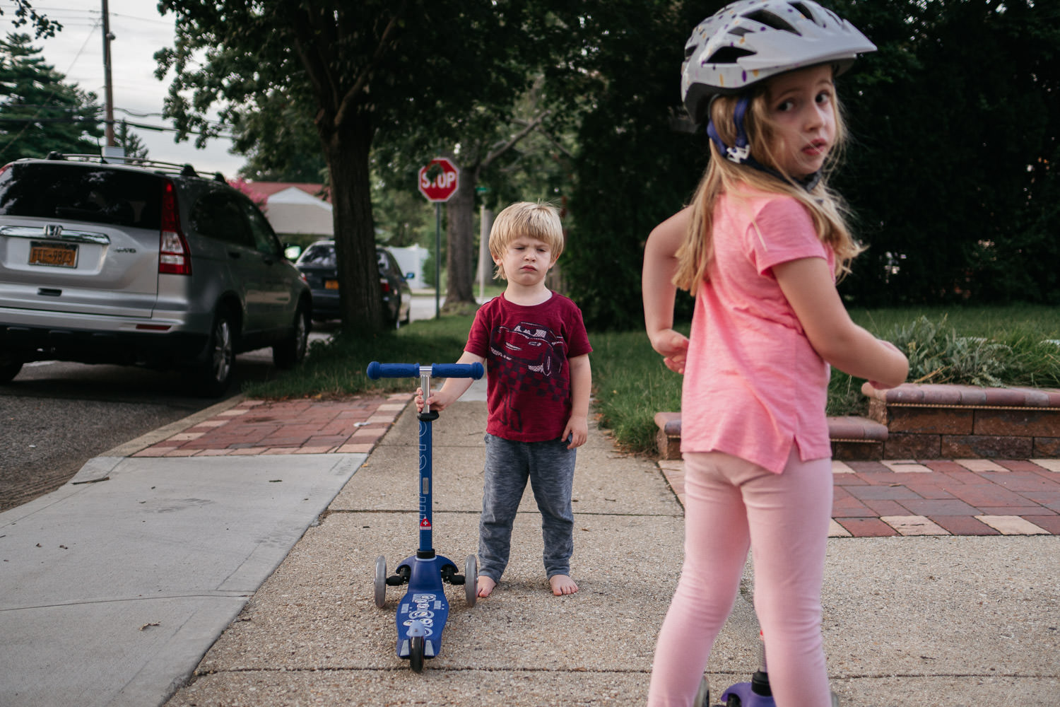 Two kids ride scooters in the driveway.